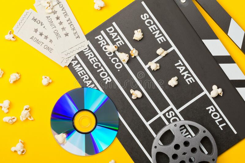 Single, black, open movie clapper or clapper-board with dvd movie disc, film reel, popcorn and movie theatre tickets flat lay top stock photos
