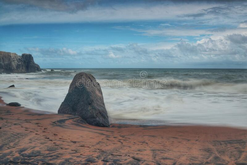 Single black rock in front of sea royalty free stock photos