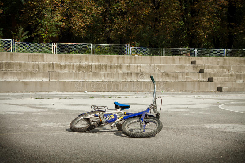 Single blue bicycle on walkway against a stone wall stock image