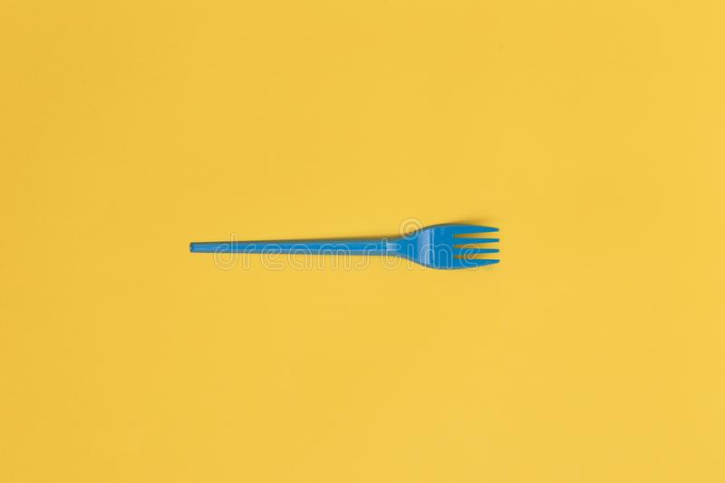 Single blue disposable fork over a yellow background.  royalty free stock images