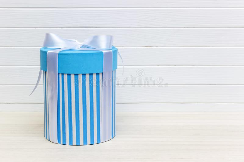 Single blue gift box on white wood table royalty free stock photo