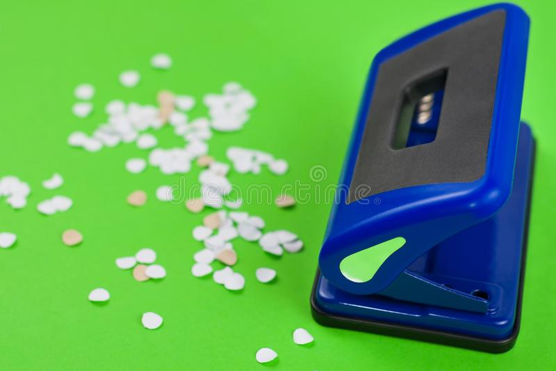 Single blue metal mechanical hole puncher and lot of round white confetti. On blank green paper stock photography