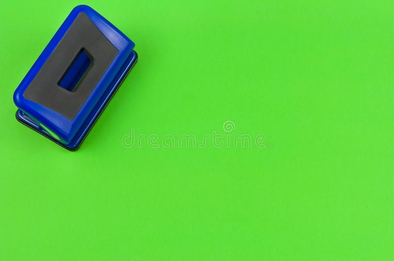 Single blue metal mechanical hole puncher. On blank green paper. Top view stock photography