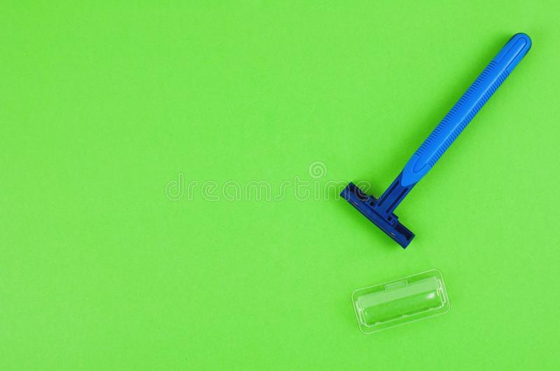 Single blue plastic disposable razor with two blades and humid strip near transparent cover on blank green paper stock images