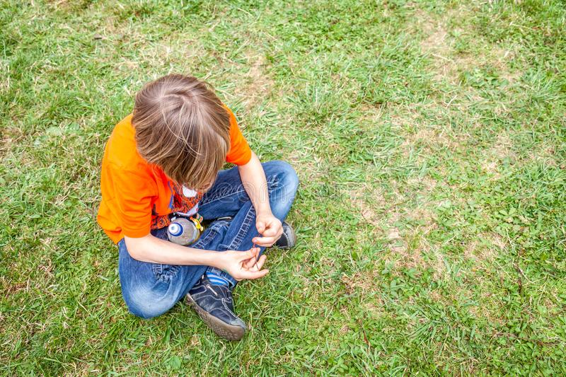 Single bored teen boy sitting on grass royalty free stock photo