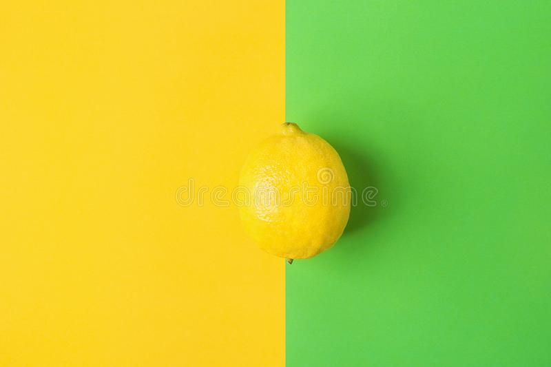 Single Bright Ripe Lemon on Contrast Background from Combination of Yellow Green Colors. Styled Creative Image. Tropical Fruit Summer Beach Party Vegan Healthy stock photos
