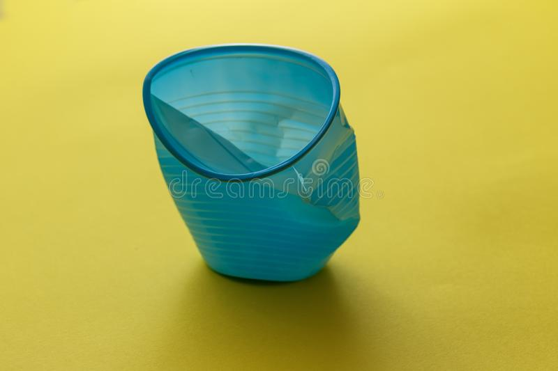Single broken blue disposable plastic cup over a yellow background.  stock photo