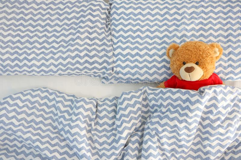 Single brown bear doll wear red shirt sleeping on the bed have space on the left side. Concept waiting for someone to sleep with h stock photos
