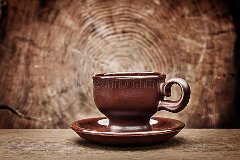 Single brown coffee cup on vintage wood background with cross cut of tree trunk stock photos