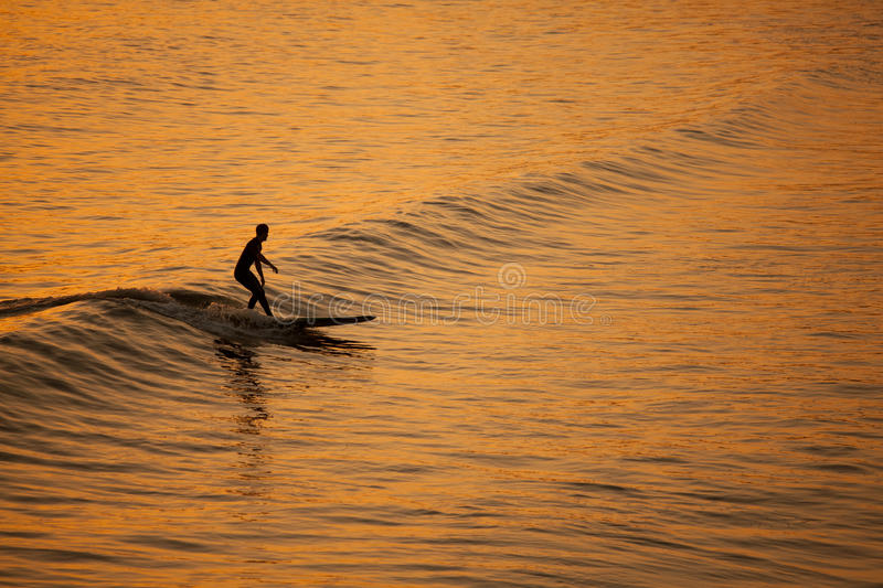 Single California surfer at sunset stock photography
