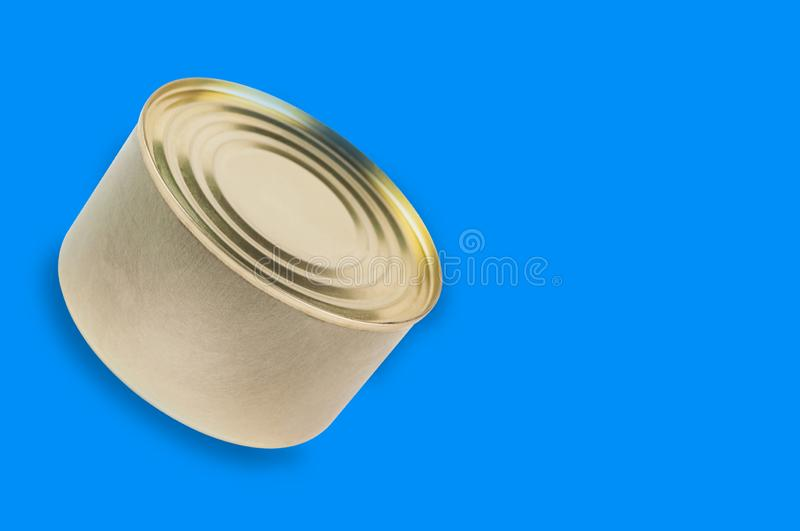 Single can of canned food on blue background with copy space. For your text royalty free stock images