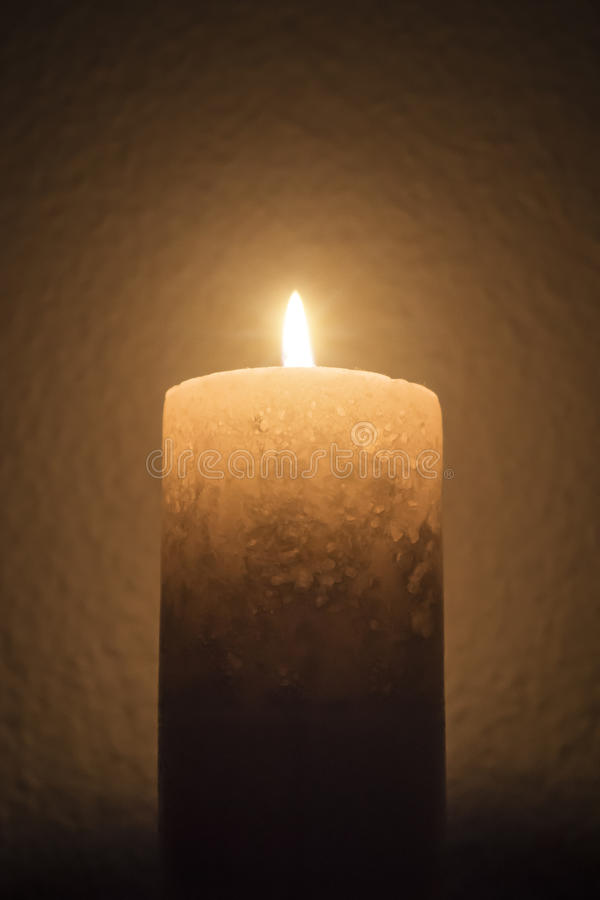 A single candle burns brightly in dark room stock images