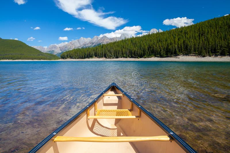 A single canoe on a mountain lake stock images