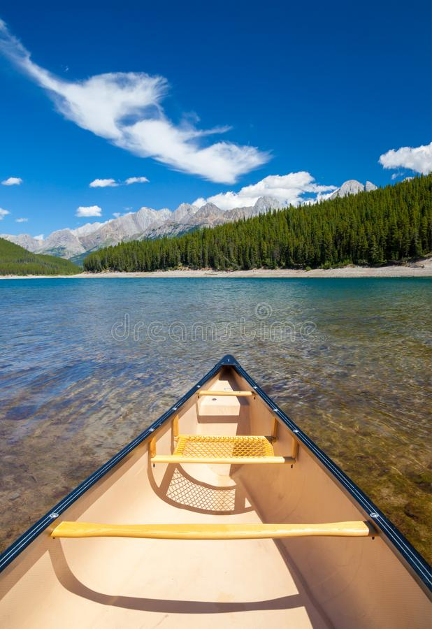 A single canoe on a mountain lake stock image