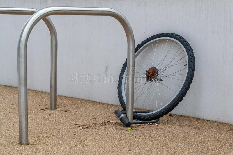 A single chained locked bicycle wheel on the street due to stealing stock images