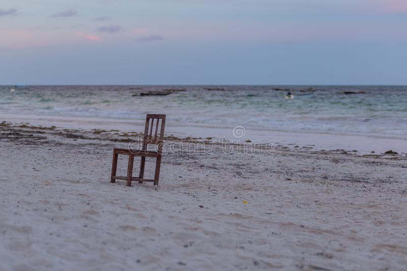 A single chair on the beach. Seascape with chair. Travel around Africa. 2018.02.21, Kiwengwa, Tanzania. Travel around Tanzania. A single chair on the beach royalty free stock images