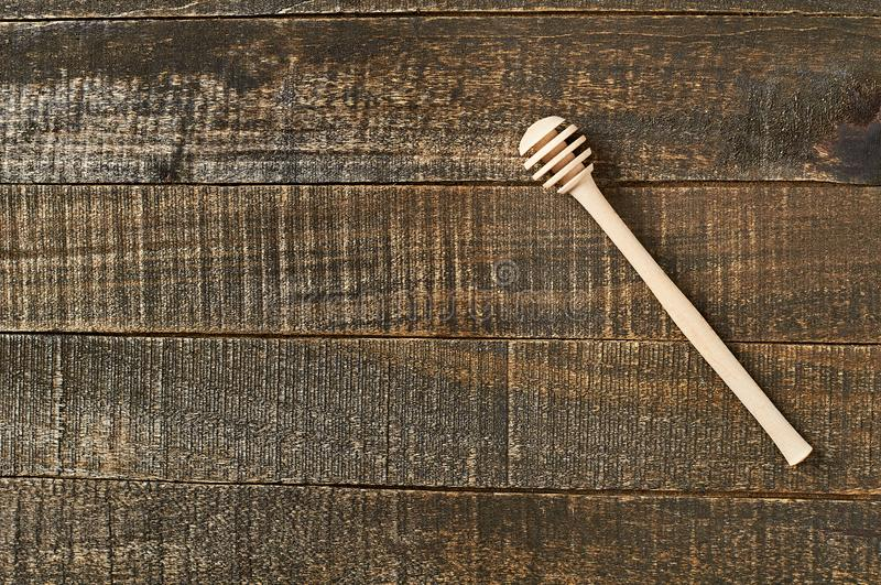 Single clean wooden dipper for honey lies on old brown rustic wooden planks. Space for text royalty free stock image