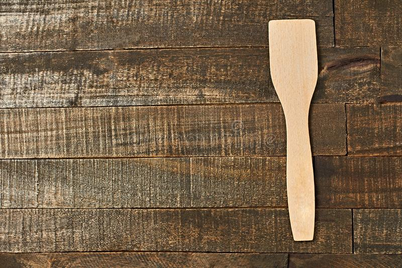 Single clean wooden spatula lies on old brown rustic wooden planks. Space for text. Top view stock photography