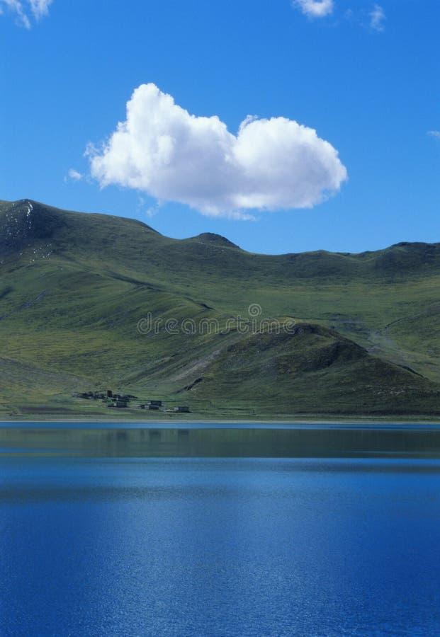 Single cloud above blue lake stock photos