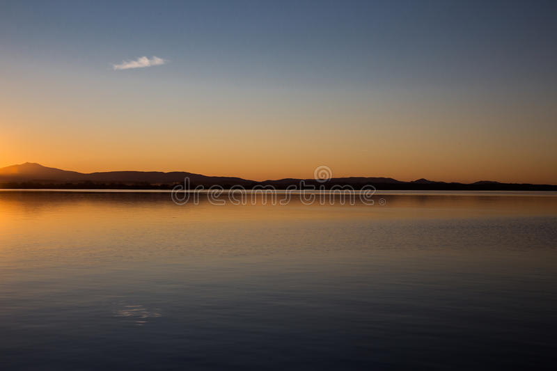 Single cloud reflectiong on a lake. An empty sky, with only a single cloud reflecting on a lake at dusk, with beautiful orange, yellow and blue colors royalty free stock image