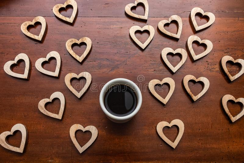 Single cup of coffe and wooden heart shapes on wooden desk. Shot from above. Love coffee royalty free stock image