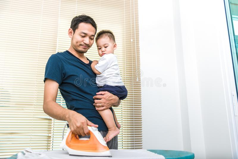 Single dad is ironing while carrying his son. People and Lifestyles concept. Single dad is ironing while carrying his son. People and Lifestyles concept stock photography