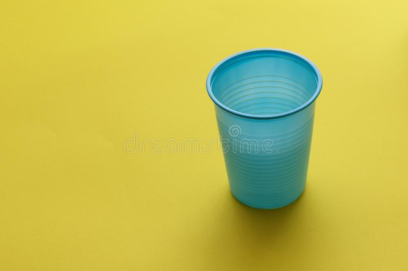 Single empty blue disposable plastic cup over a yellow background.  stock images