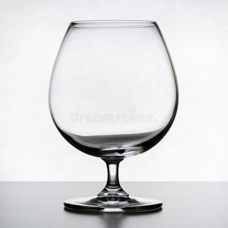 Single empty brandy glass on white background. stock photo