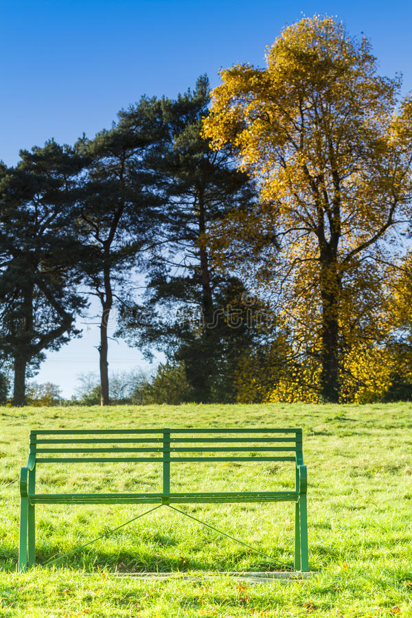 Single empty green seat in a meadow. Single empty green metal seat in a meadow on a sunny autumn day stock photography
