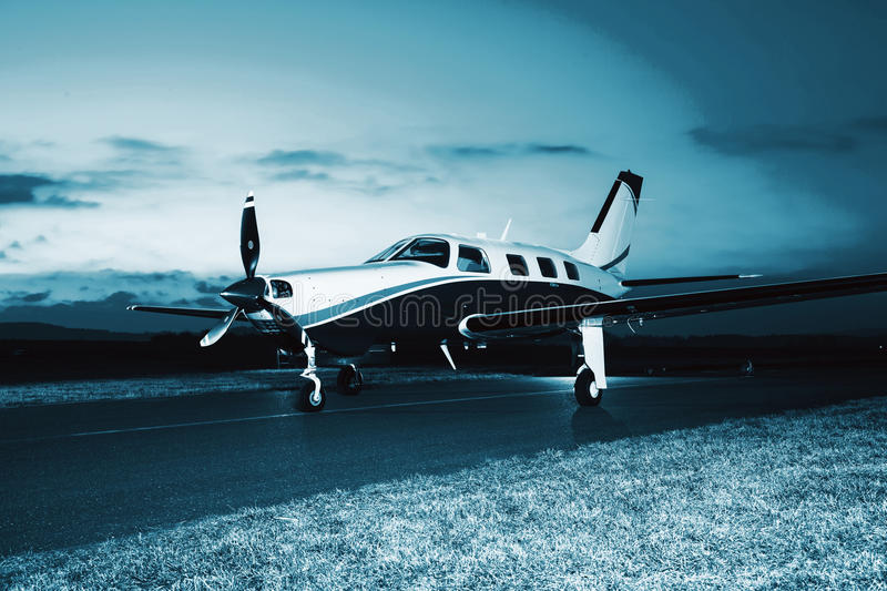 Single engine piston aircraft. Small private single-engine piston aircraft on runway during sunset stock images