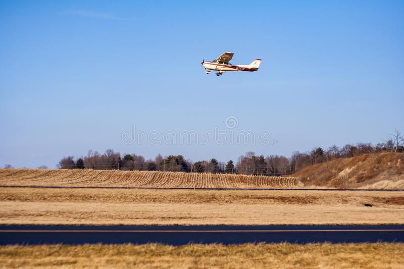 Single Engine Propeller Plane Flying Over Runway in Autumn royalty free stock photo