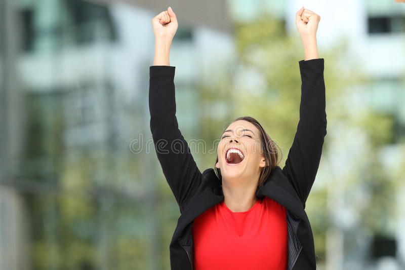 Excited executive raising arms after success stock image