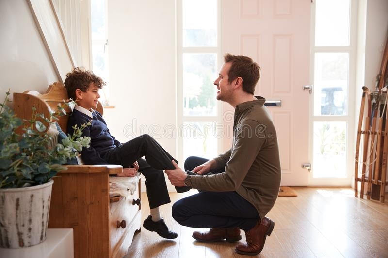 Single Father At Home Getting Son Wearing Uniform Ready For First Day Of School royalty free stock photo