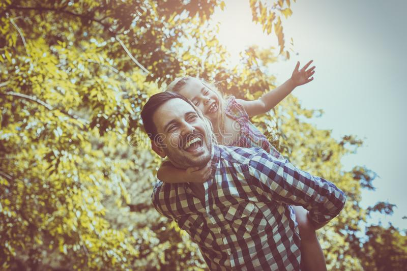 Single father with little daughter in meadow. Little girl lying stock image