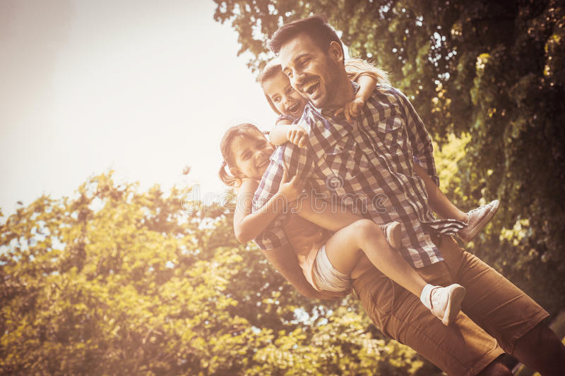 Single father playing in nature with his daughter. royalty free stock images