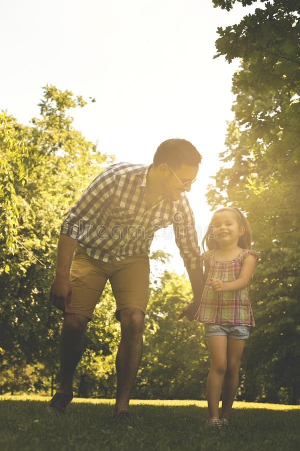 Single father running in the meadow with daughter. stock image