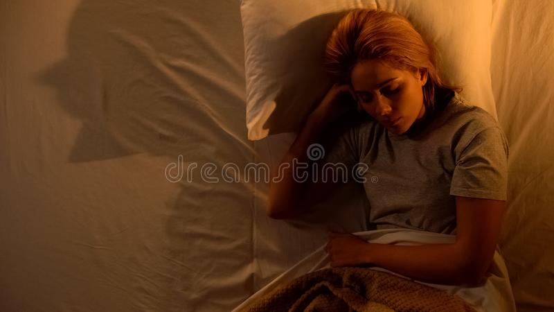 Single female sleeping in bed, suffering nightmares, monster shaped shadow, fear royalty free stock photo