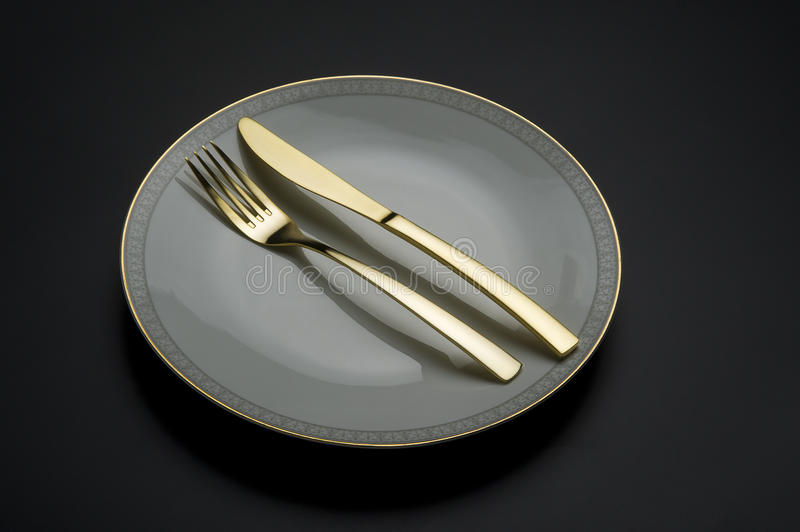 Single fine china plate with knife and fork stock photography