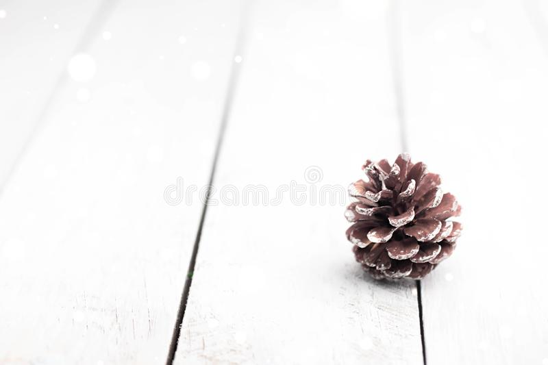 Single fir cone on white wooden table with sparkling flares and blurred background. Christmas decorations. royalty free stock images