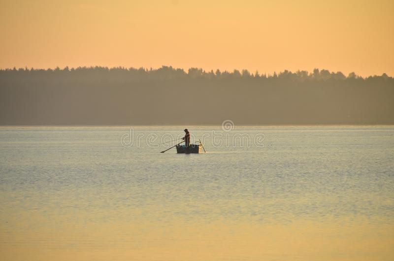 A single fisherman in a small boat in calm water in smooth evening light. A quiet, idyllic scene in pastel purple light. it`s a lonely fisherman, fishing in the royalty free stock image