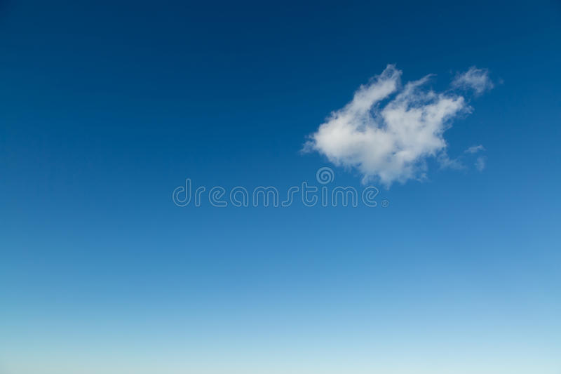 Single fluffy white cloud against deep blue sky. Single fluffy white cloud set against a deep blue mediterranean sky royalty free stock image