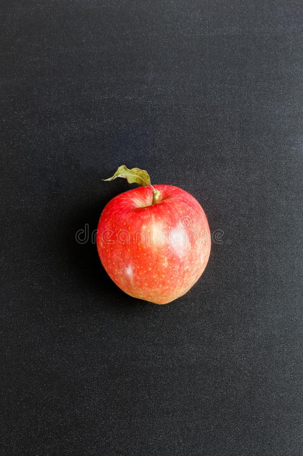 Single fresh red apple on black chalkboard background royalty free stock photos