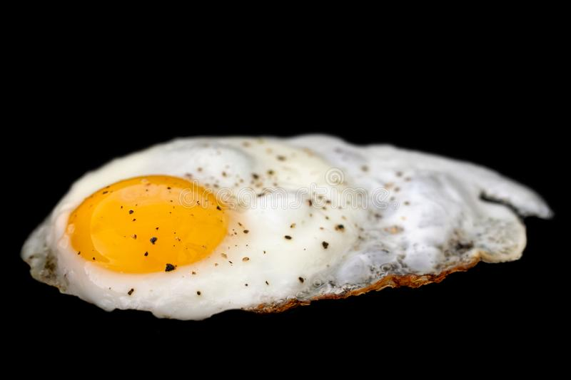 Single fried egg sprinkled with ground black pepper isolated on. Black stock photography