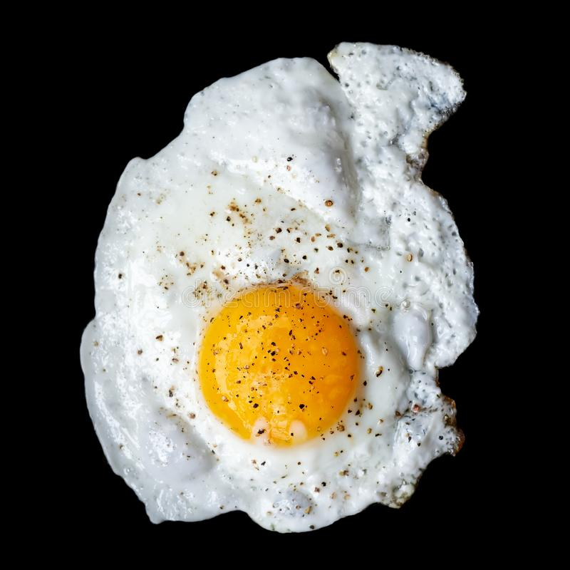 Single fried egg sprinkled with ground black pepper isolated on. Black from above royalty free stock image