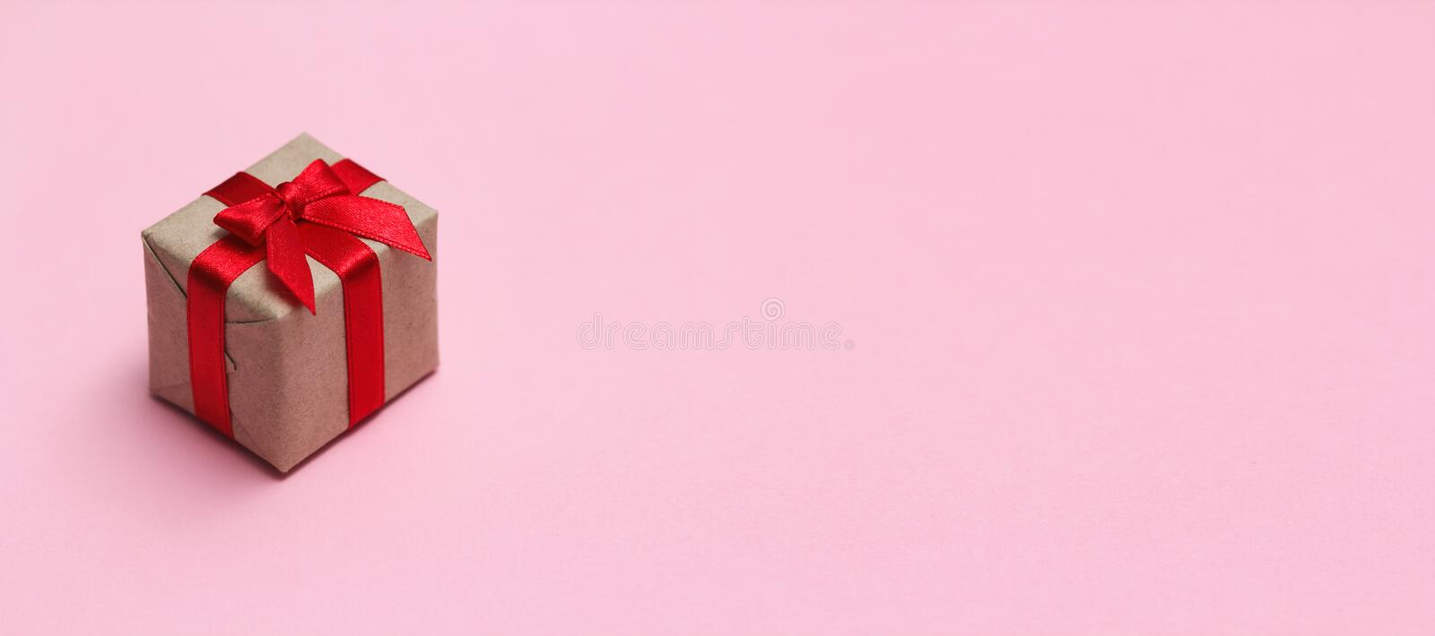 Single gift box on pink solid background. Sale concept. Long horizontal banner photo format. Your text space stock image