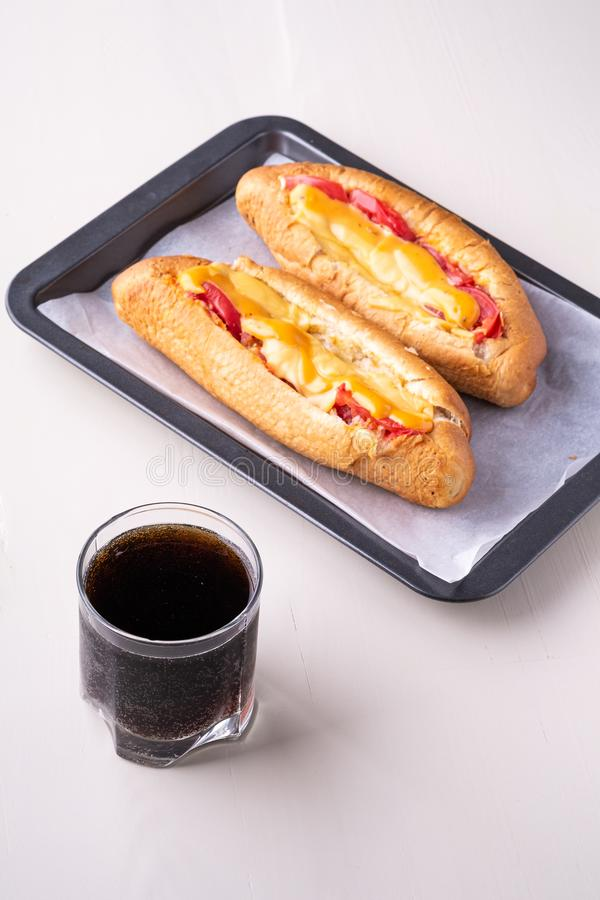 Single glass of cola drink with two hot dog fast food junk fresh sausage cheese sauce isolated on baking tray white background. Close up royalty free stock photography