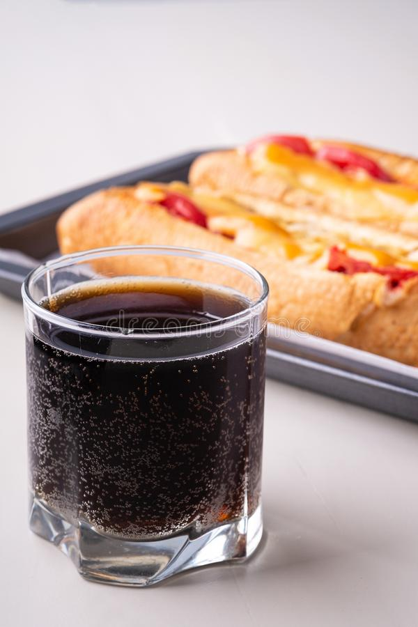 Single glass of cola drink with two hot dog fast food junk fresh sausage cheese sauce isolated on baking tray white background stock images