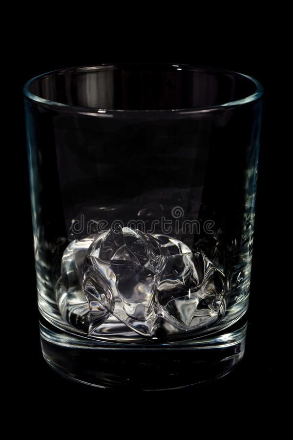 Single glass with ice cube stock photography
