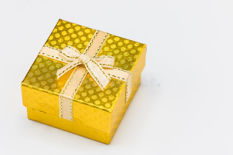 Single Gold gift box with silver ribbon on white background. royalty free stock images
