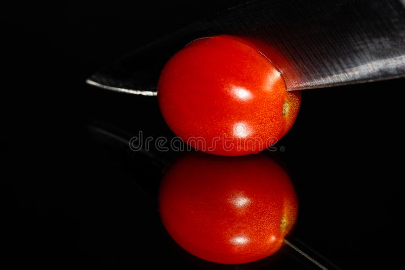 A single grape tomato on a highly reflective surface being sliced by a knife on a black background with vibrant colors stock image